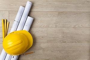 hardhat and blueprints on wood floor