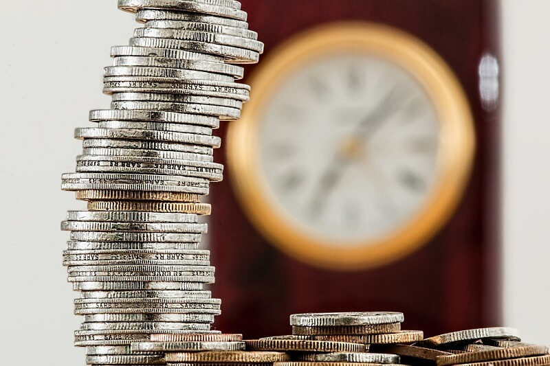 Stack of coins and clock background