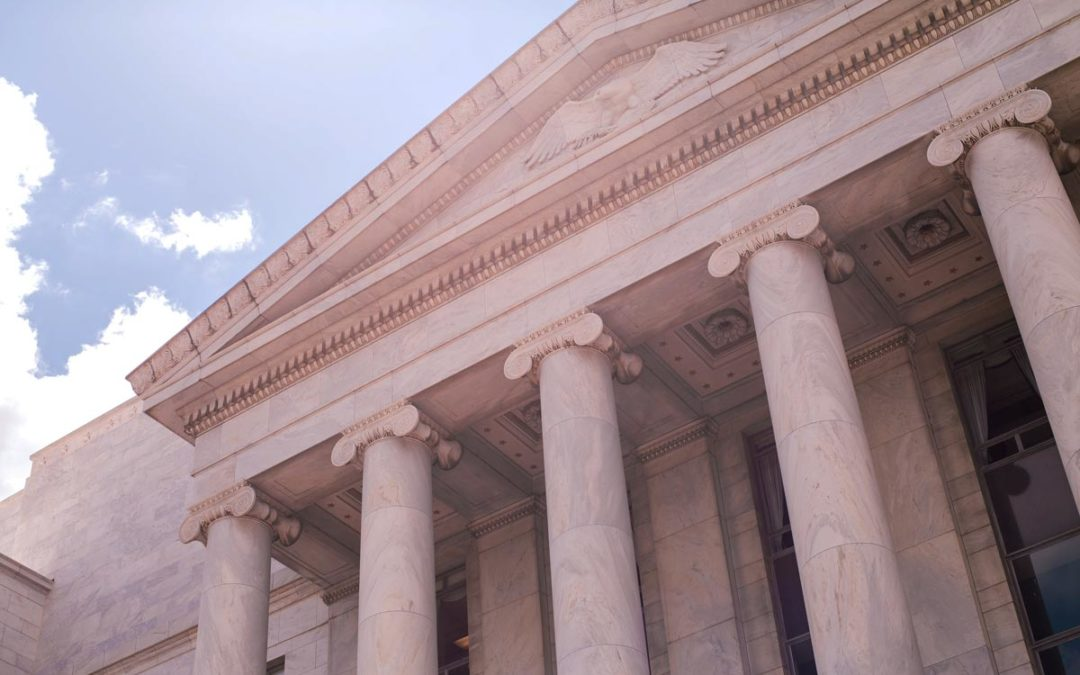 Front of a government capitol looking up at sky.
