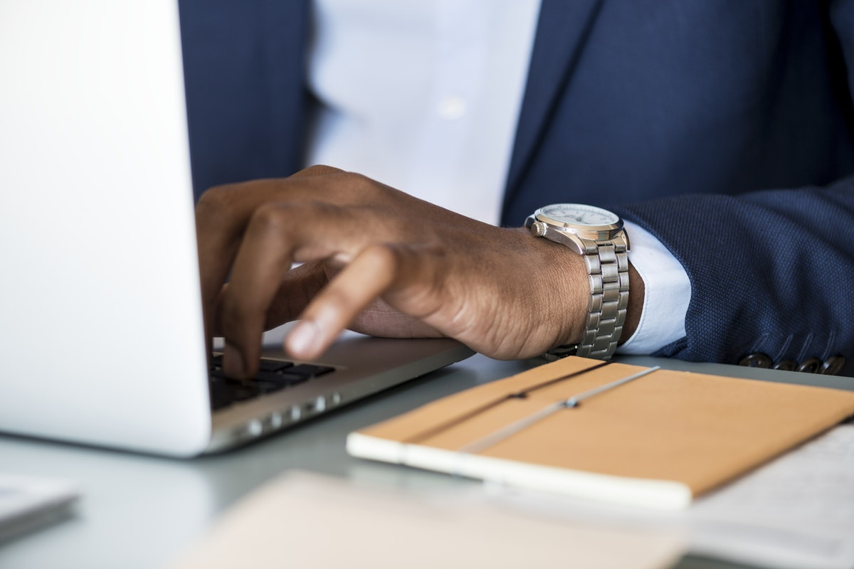 tan male hands typing on a laptop