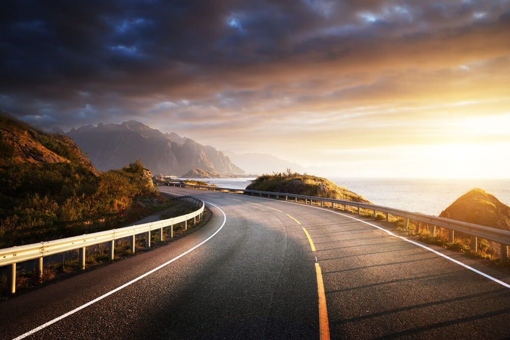 Curved road by ocean at sunset.