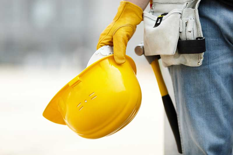 Contractor holding a hardhat and tools